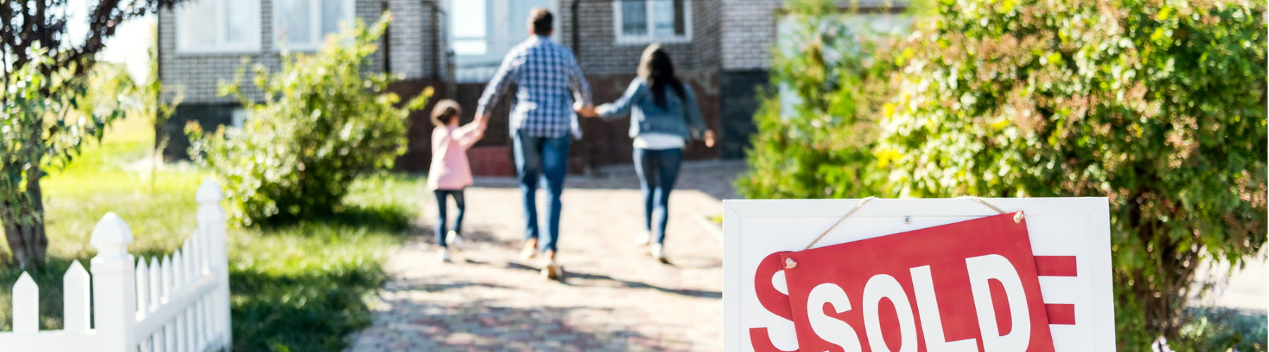Personal insurance represented by family posing walking into new home